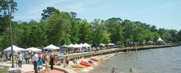 Tents and exhibitors line the sidewalk along the shore of Mobile Bay during Earth Day festivities at Fairhope.
